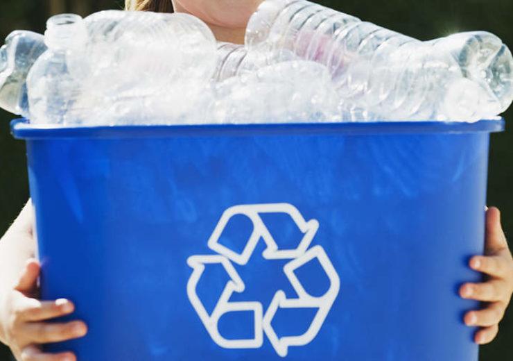 Little Girl Holding Recycling Bin.