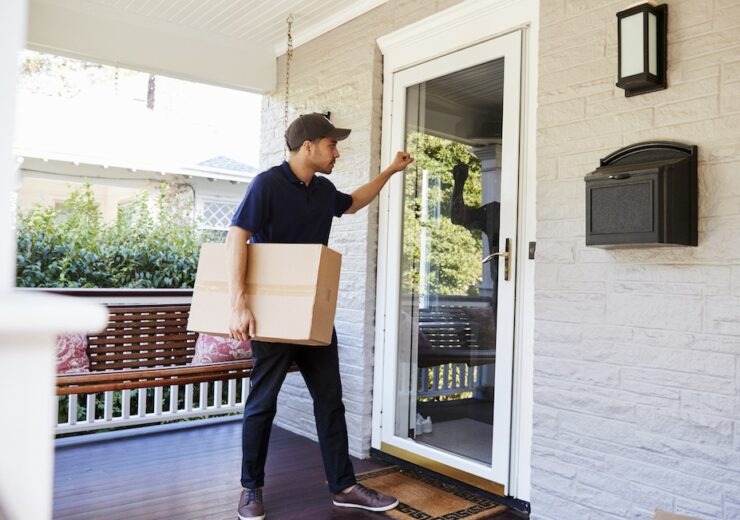 Courier Knocking On Door Of House To Deliver Package